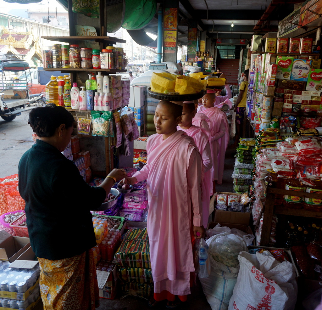 In this Jan. 25, 2017 photo, Buddhist nuns make their way through Mawlamyine's central market during their daily rounds to collect alms...