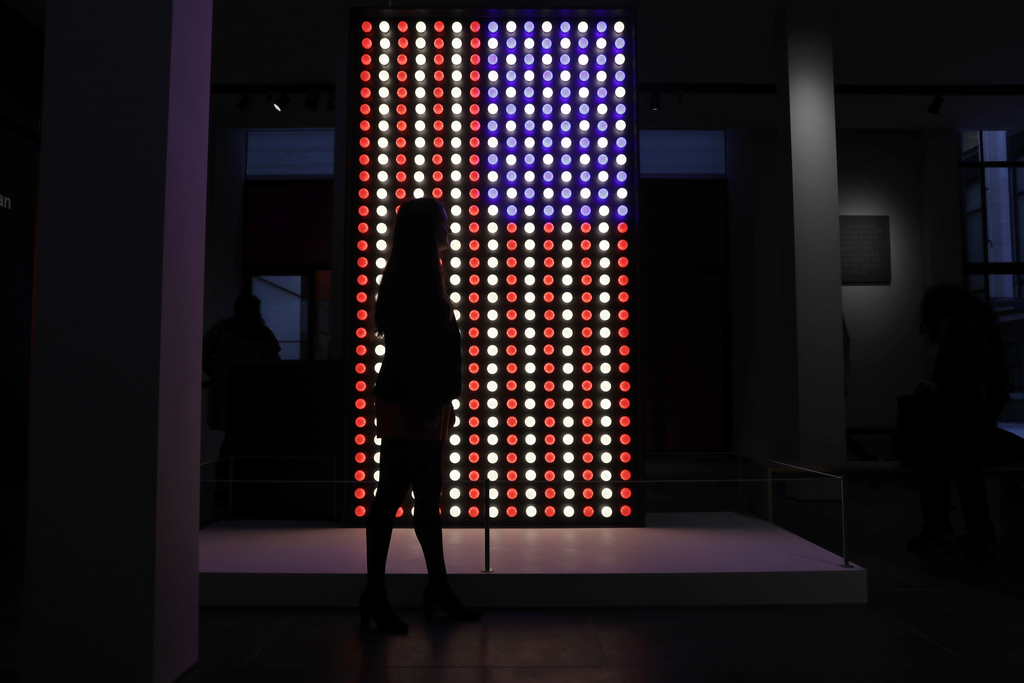 """A British Museum representative poses for photographs next to an illuminated American flag at the entrance of """"The American Dream: pop ..."""