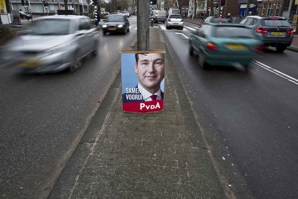 In this Friday, March 3, 2017 photo, an election poster showing Lodewijk Asscher, from the Labour Party, PvdA, is placed on a street me...