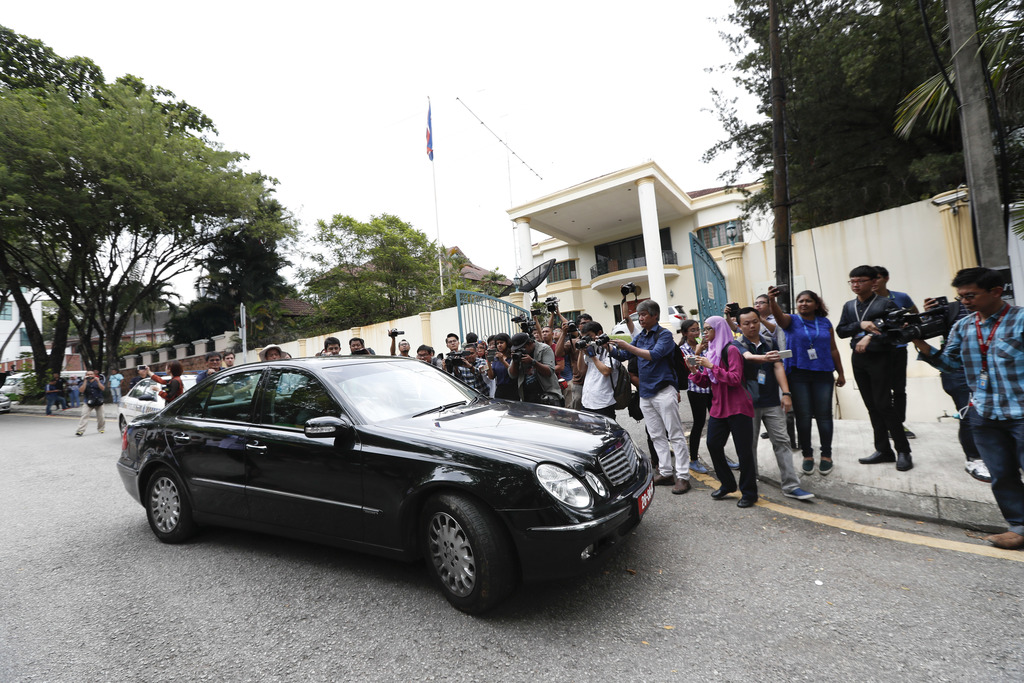 Journalists chase a North Korean diplomatic vehicle as it leaves the North Korean Embassy in Kuala Lumpur, Malaysia, Tuesday, March 7, ...