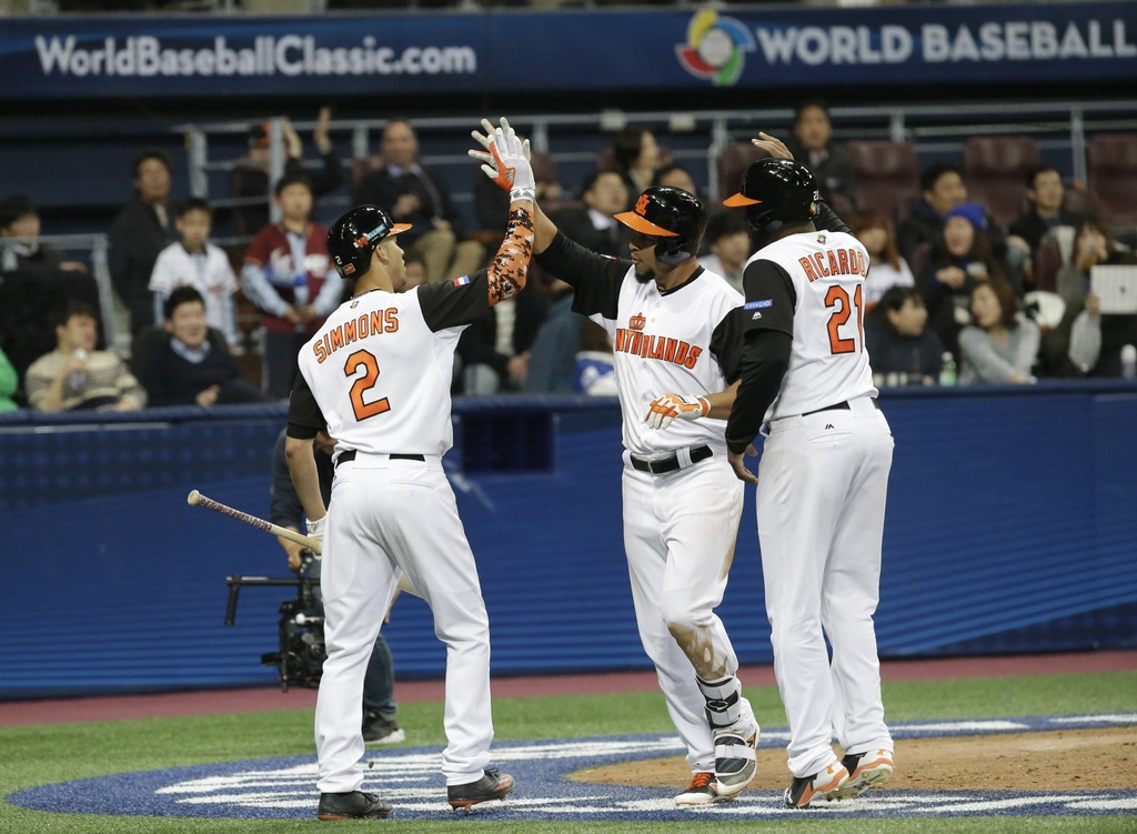 Netherlands's Randolph Oduber, center, celebrates with Andrelton Simmons and Dashenko Ricardohits, right, after hitting a two-run home ...