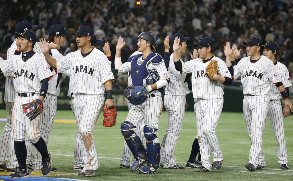 Japan's catcher Seiji Kobayashi, center, celebrates with teammates after beating Cuba 11-6 in their first round game of the World Baseb...