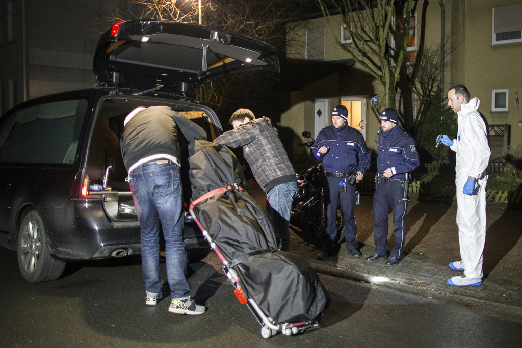 Undertakers lift a stretcher with a bodybag into a hearse in Herne, Germany, Tuesday, March 7, 2017. German police said Tuesday they ha...