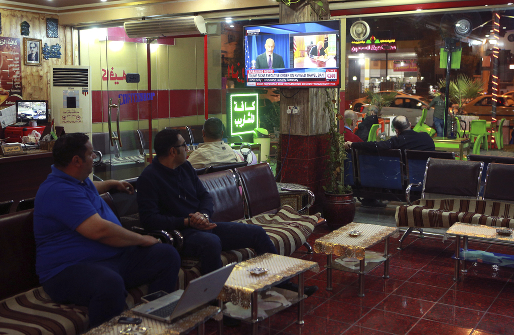 Men watch the news on television at a cafe in Baghdad, Iraq, Monday, March 6, 2017. Iraq has welcomed its removal from a revised U.S. t...
