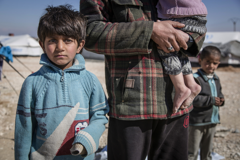 In this picture taken, Feb. 16, 2017, a Syrian school teacher from Deir Ezzour, stands with his son and daughter in Al Hol Camp, Hasaka...