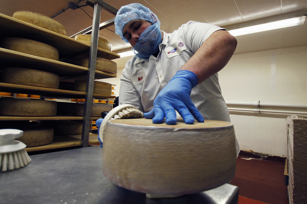 In this Feb. 27, 2017, photo, Nick Brummel prepares a wheel of Grand Cru Surchoix cheese at the Emmi Roth USA production plant in Monro...