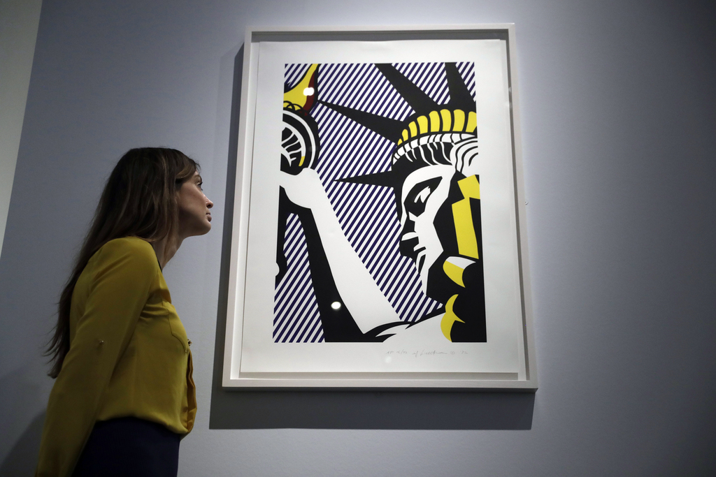 """A British Museum representative poses for photographs next to Roy Lichtenstein's """"I Love Liberty"""" which features in """"The American Dream..."""