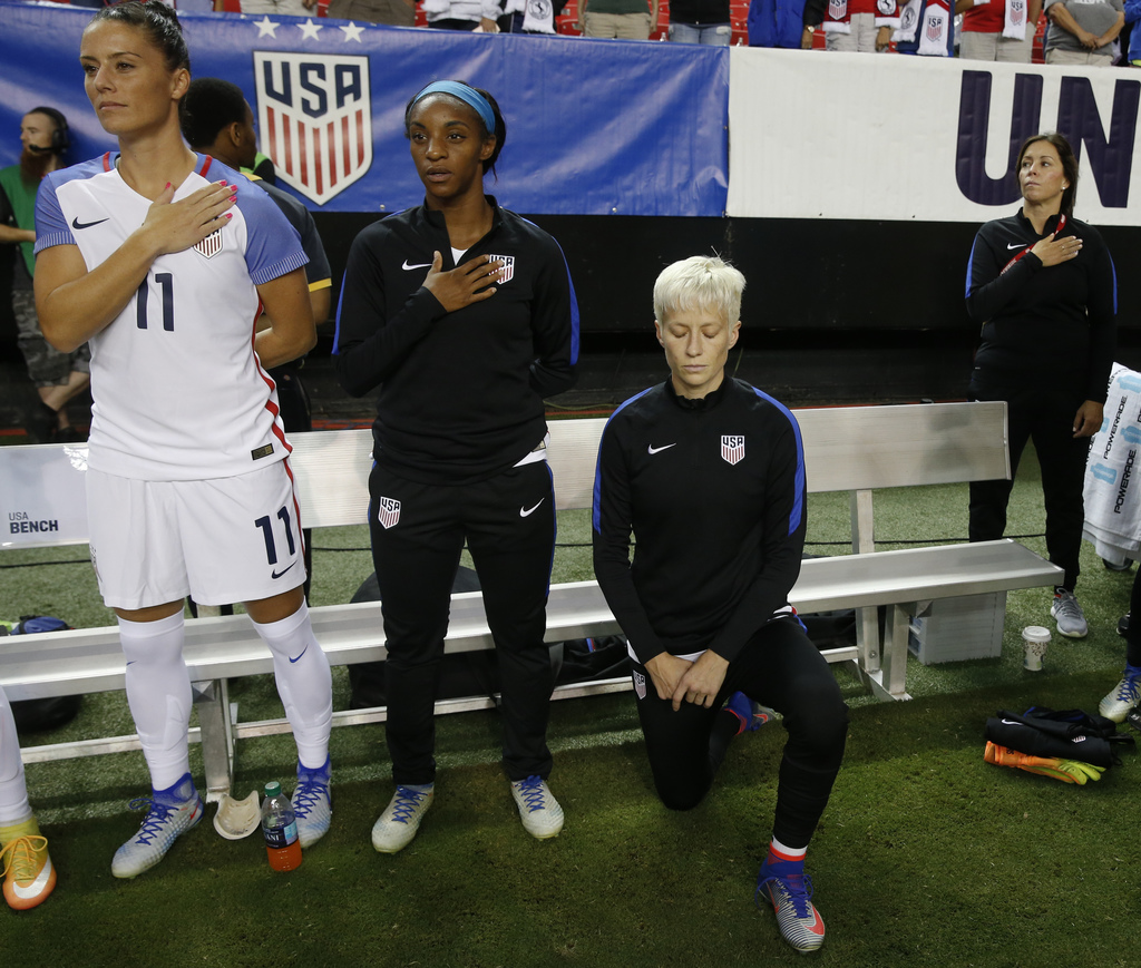 FILE - In this Sunday, Sept. 18, 2016 file photo, United States' Megan Rapinoe, right, kneels next to teammates Ali Krieger (11) and Cr...