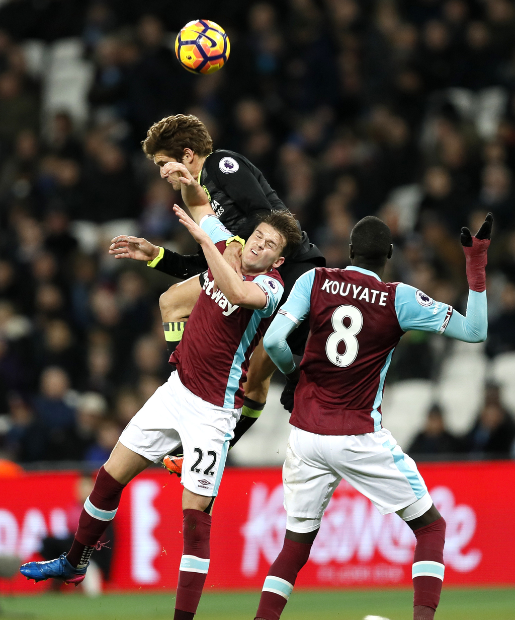 Chelsea's Marcos Alonso leaps above West Ham's Sam Byram and West Ham's Cheikhou Kouyate, right, to head the ball during the English Pr...