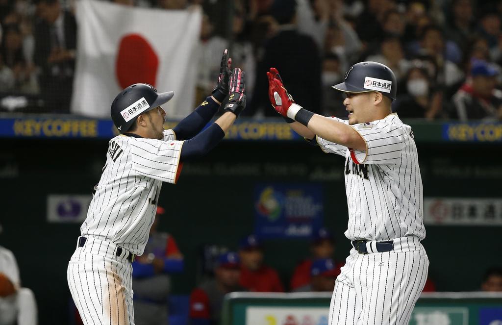 Japan's Yoshitomo Tsutsugo, right, celebrates with teammate Ryosuke Kikuchi after hitting a two-run shot against Cuba's pitcher Jonder ...