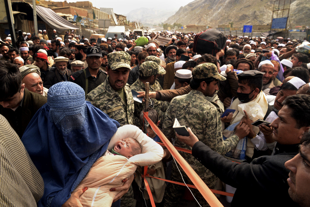 Pakistani security personnel check Afghan nationals as they prepare to leave to Afghanistan, at Pakistan's Torkham border, Tuesday, Mar...