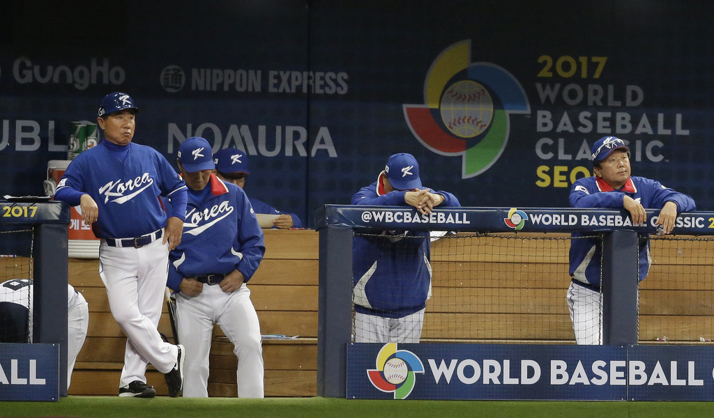 South Korea's Manager Kim In-sik, second from right, lowers his head after the 8th inning of the first round game against Netherlands a...