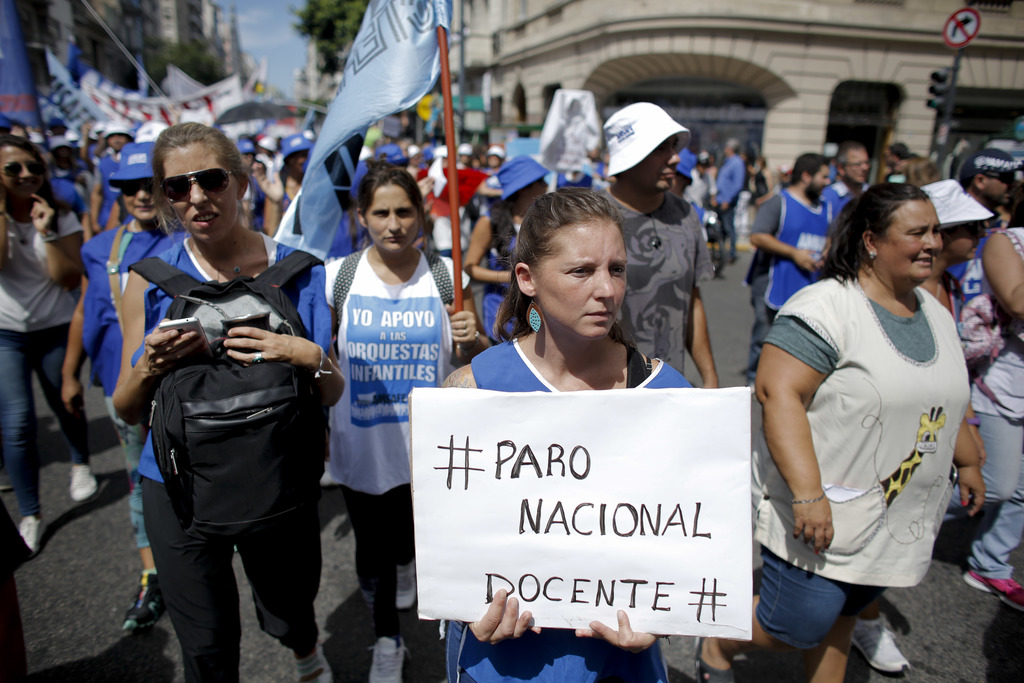 """A teacher holds a sign that reads in Spanish """"National teachers' strike"""" during a protest in Buenos Aires, Argentina, Monday, March 6, ..."""