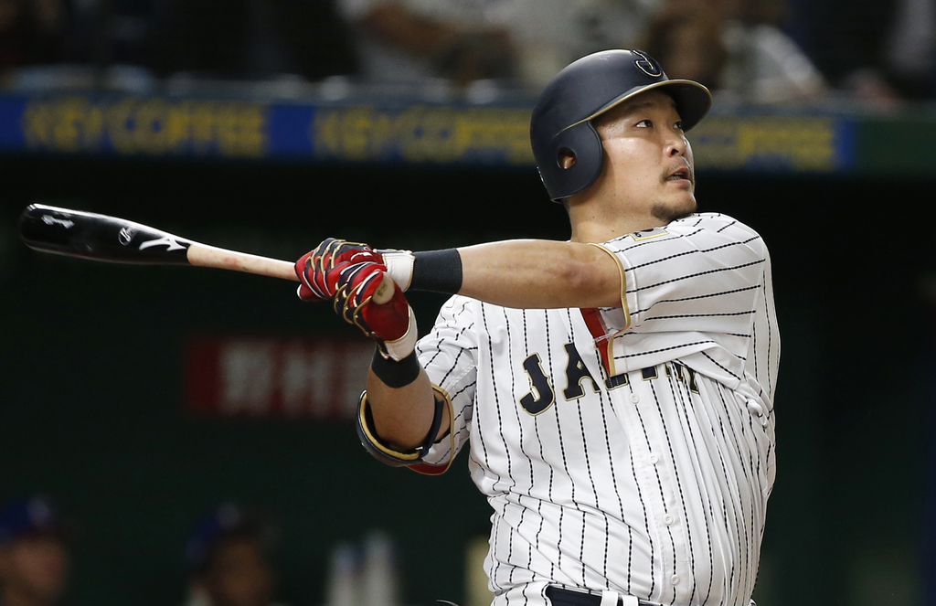 Japan's Yoshitomo Tsutsugo hits a two-run shot against Cuba's pitcher Jonder Martinez in the seventh inning of their first round game o...
