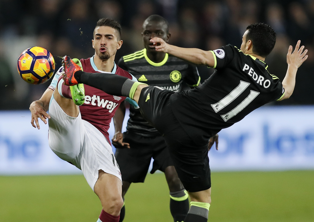 West Ham's Manuel Lanzini, left, and Chelsea's Pedro battle for the ball during the English Premier League soccer match between West Ha...