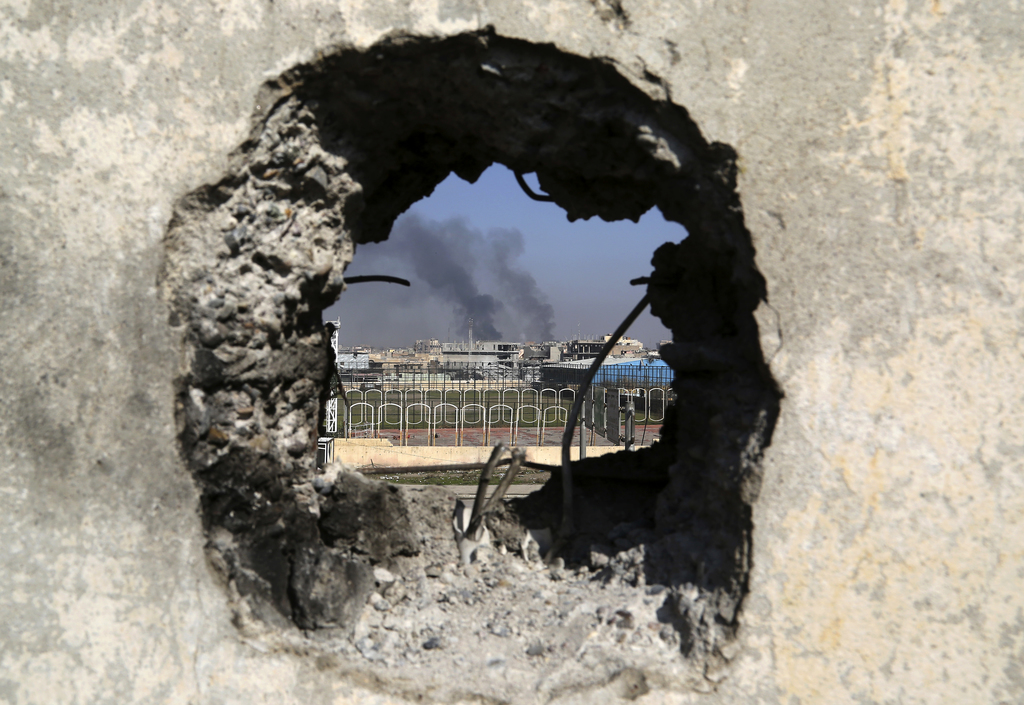 Smoke rises from government complex, seen through a hole in a wall that made by Iraqi forces to fire their weapons, as Iraqi security f...