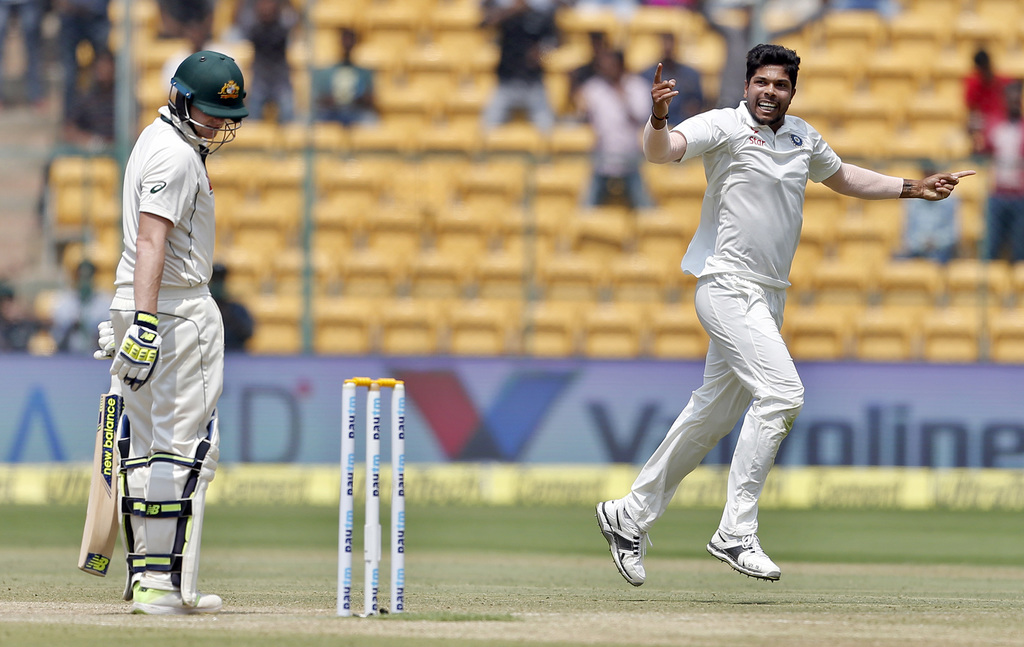 India's Umesh Yadav, right, celebrates the dismissal of Australia's captain Steven Smith, left, during the fourth day of their second t...