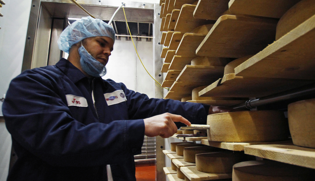 In this Feb. 27, 2017, photo, Jon Conkey cuts a piece from a wheel of Grand Cru Surchoix cheese at the Emmi Roth USA production plant i...