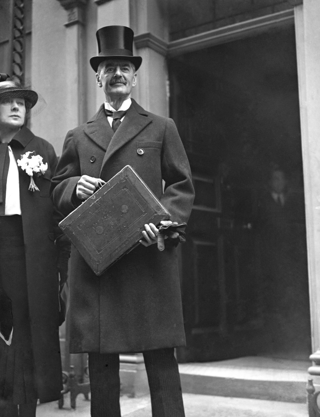 FILE - In this April 21, 1936 file photo, Britain's Chancellor of the Exchequer Neville Chamberlain  as he stands with his red budget b...