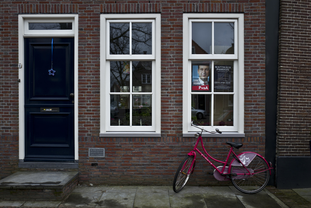 In this Friday, March 3, 2017 photo, an election poster showing Lodewijk Asscher, from the Labour Party, PvdA, is displayed on the wind...