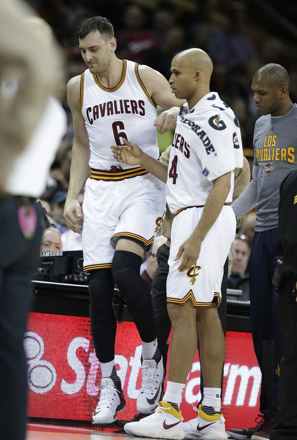 Cleveland Cavaliers' Andrew Bogut (6) is helped up by Cleveland Cavaliers' Richard Jefferson (24) in the first half of an NBA basketbal...