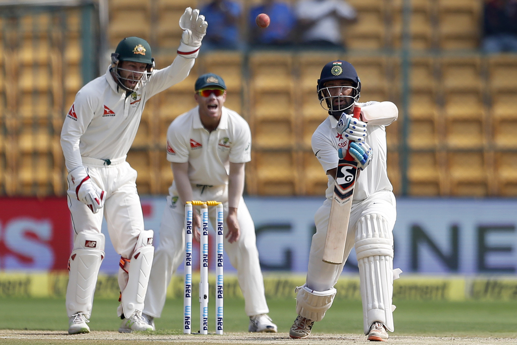 Australia's Matthew Wade, left, and David Warner, center, react as India's Cheteshwar Pujara plays a shot during the fourth day of thei...