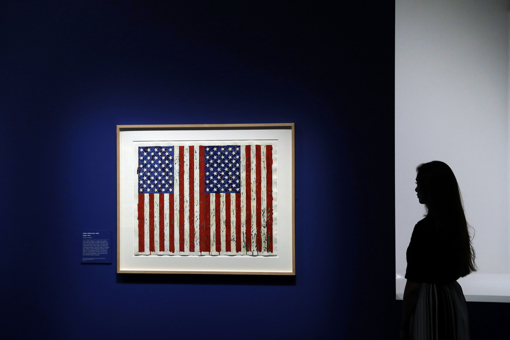 """A British Museum representative poses for photographs next to """"Flag I"""" by Jasper Johns which features in """"The American Dream: pop to th..."""