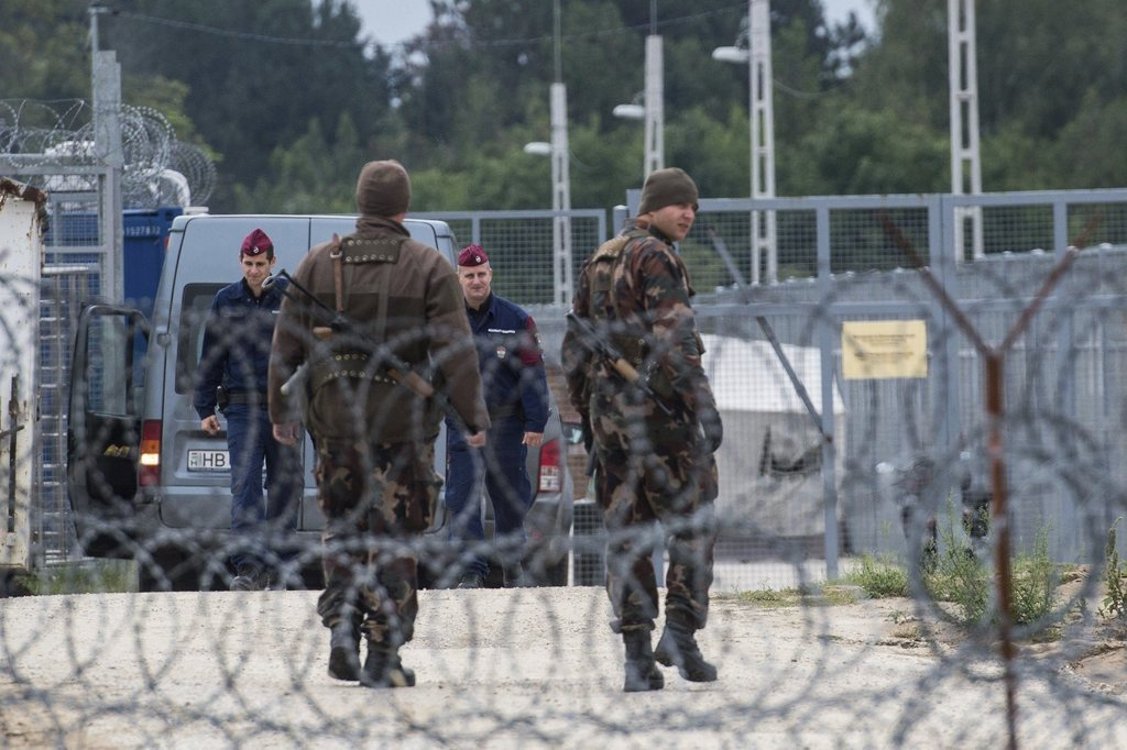 FILE - In this Sept. 21, 2016 file photo Hungarian soldiers, front, and police officers patrol at the transit zone at Hungary's souther...