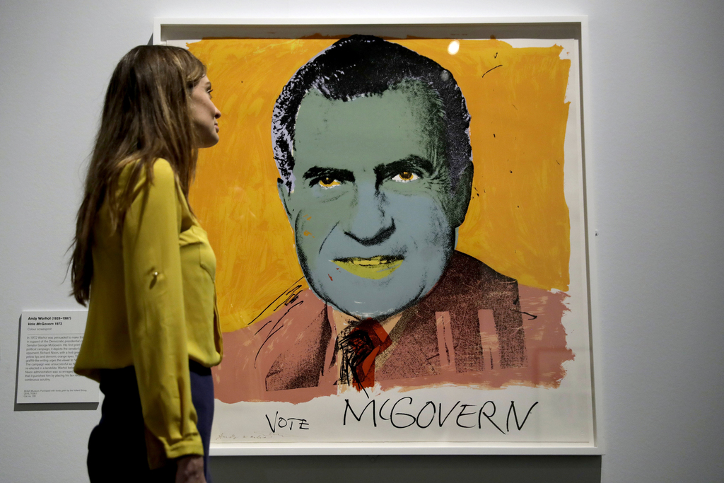 """A British Museum representative poses for photographs next to """"Vote McGovern"""" by Andy Warhol which features in """"The American Dream: pop..."""