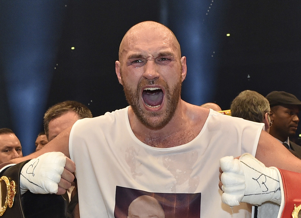 FILE - In this file photo dated Sunday, Nov. 29, 2015, Britain's new world champion Tyson Fury celebrates with the WBA, IBF, WBO and IB...