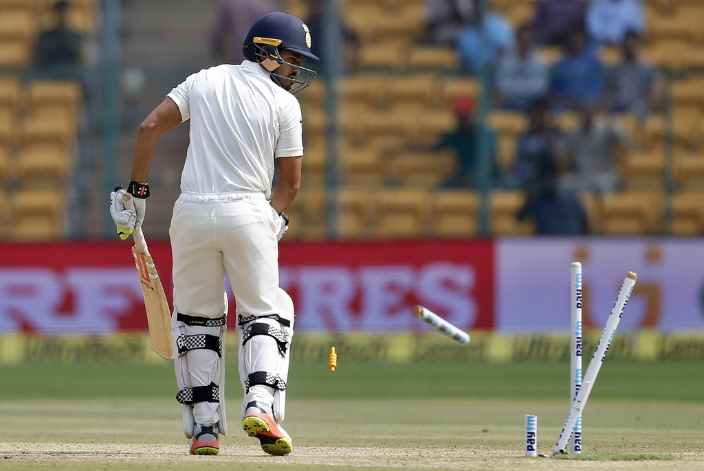 India's Karun Nair looks at the broken stumps after he was bowled out by Australia's Mitchell Starc during the fourth day of their seco...