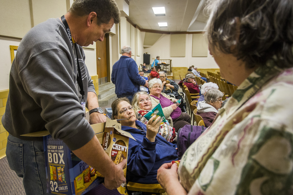 Southern Baptist Disaster Relief Chaplain Jeff Thompson passes bags of chips to, from left to right, Suzanne Morgan, Carol Shaylor and ...