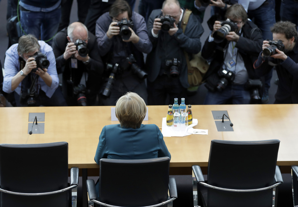 Photographers take pictures as German Chancellor Angela Merkel, front, arriving  for a questioning at a parliament committee,  investig...