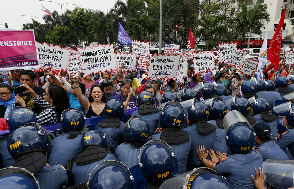 Police block women during a rally at the U.S. Embassy to mark International Women's Day Wednesday, March 8, 2017 in Manila, Philippines...