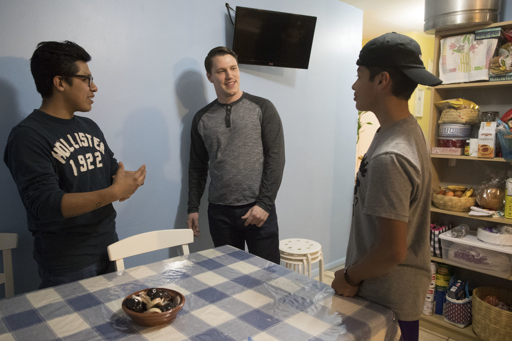 In this Tuesday, Feb. 28, 2017 photo, Jesse Silverberg, center, Axel Juarez, left, and his brother Jose talk to each other before dinne...