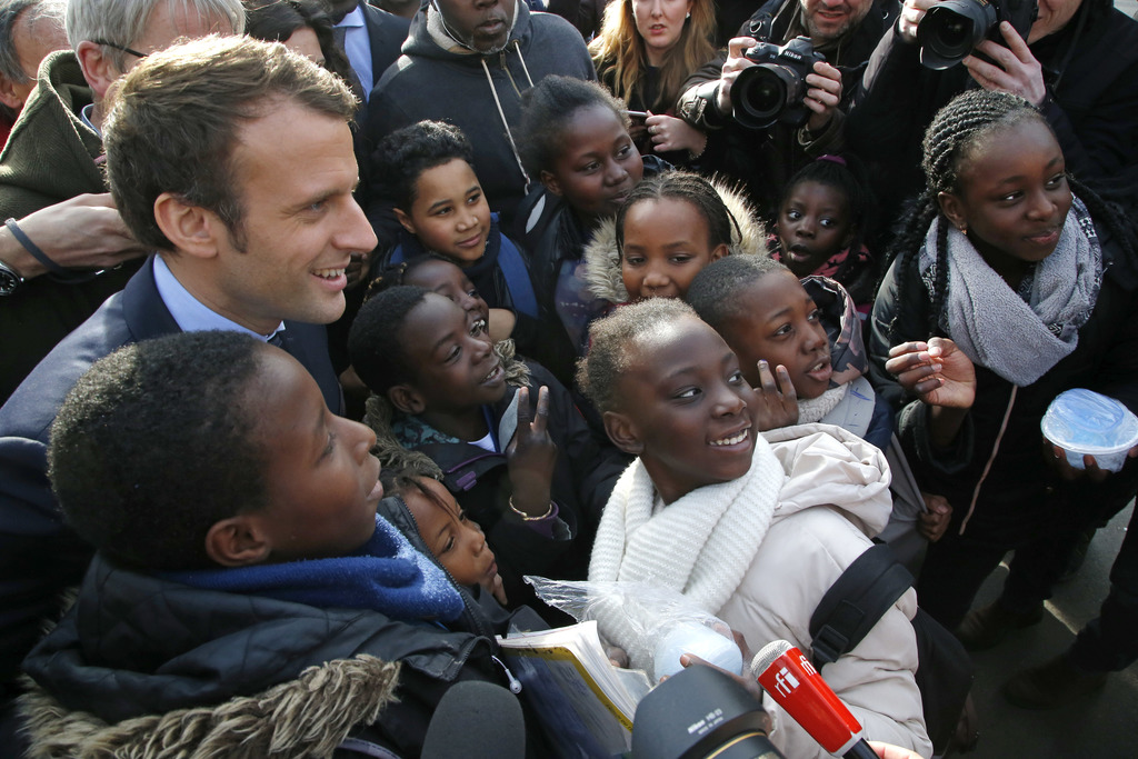 Independent centrist presidential candidate Emmanuel Macron poses with students of the Moliere school for a group photo in Les Mureaux,...