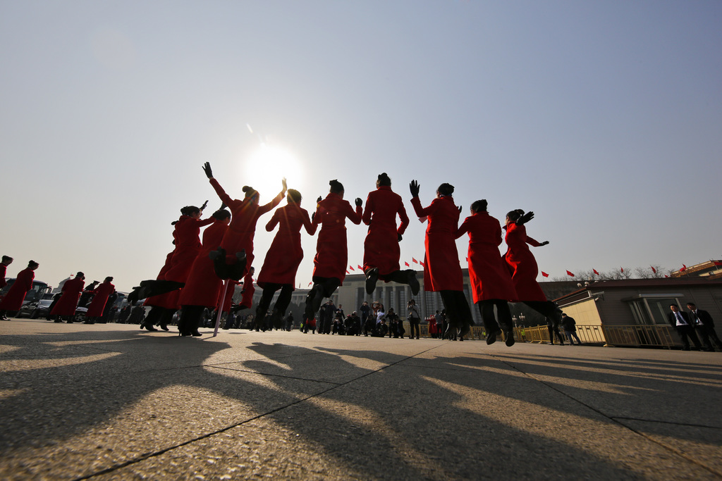In this Friday, March 3, 2017 photo, hospitality staff jump as they pose for photographs on Tiananmen Square during the Chinese People'...