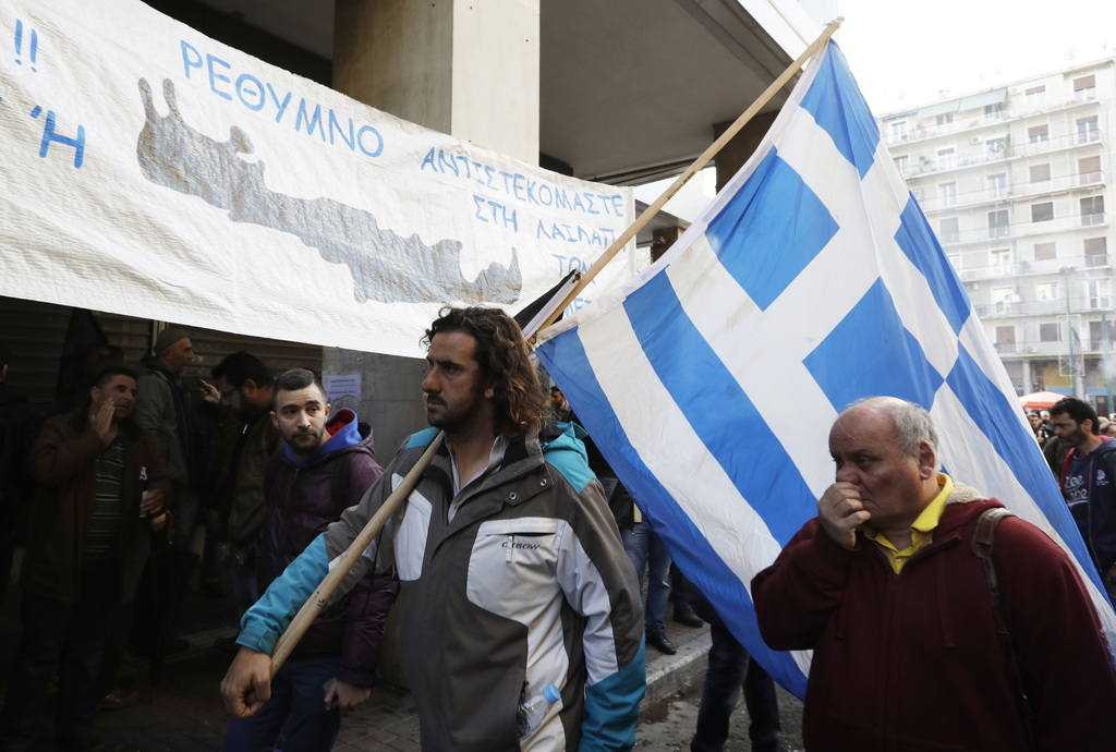 A protester holds a Greek flag as farmers gather outside the Greek Agriculture Ministry, in Athens, Wednesday, March 8, 2017. Several h...