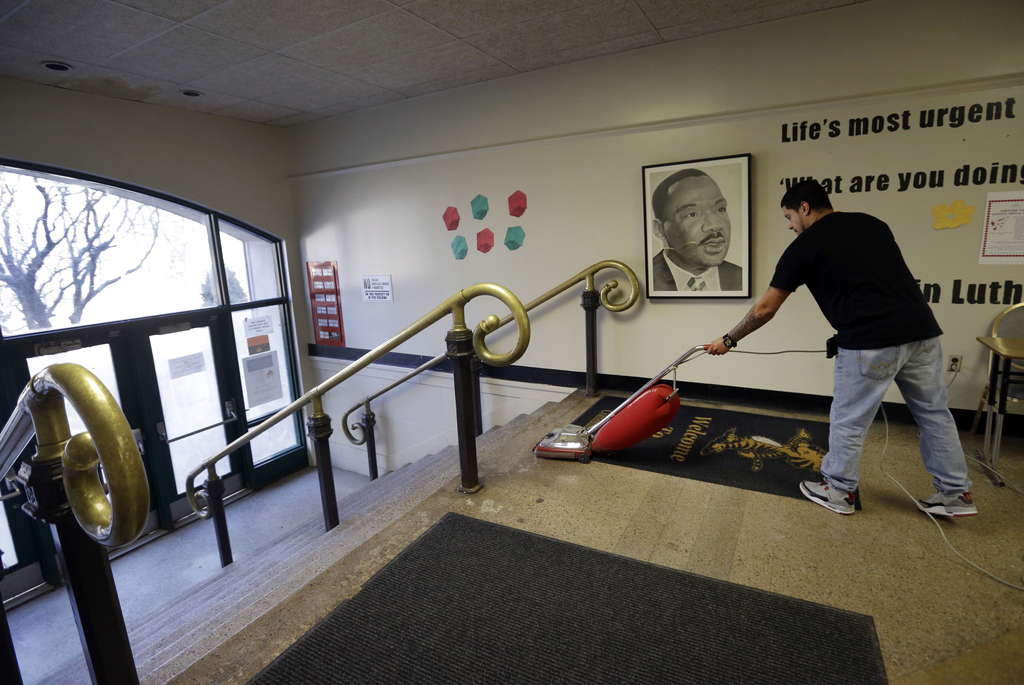 In this Feb. 23, 2017 photo, custodian Mike Cruz vacuums the lobby of the Martin Luther King Jr. A proposal to shutter the hollowed-out...