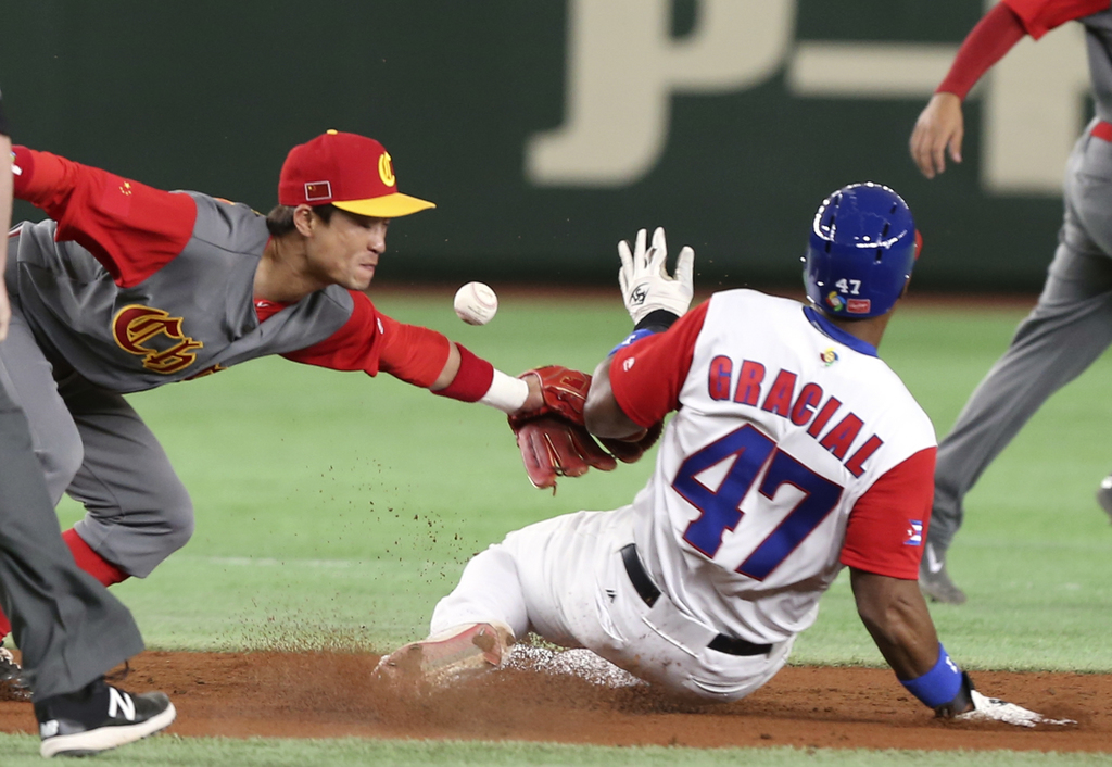 Cuba's Yurisbel Gracial steals into second as China's second baseman Du Xiaolei, left, cannot tag out during the second inning of their...