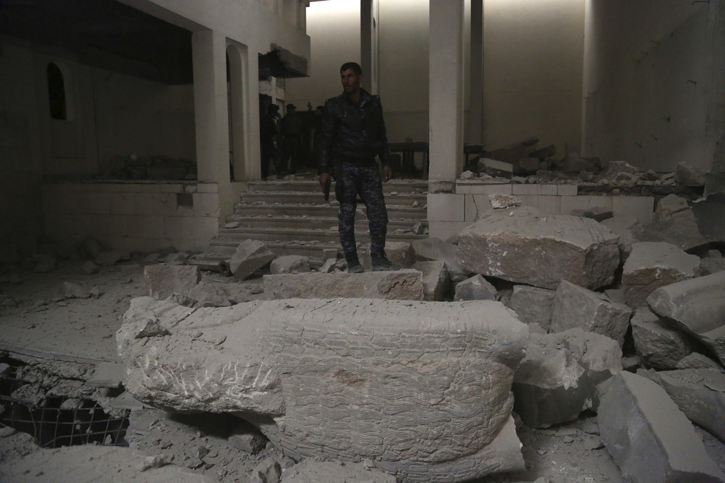 Iraqi federal police inspect the inside of Mosul's heavily damaged museum. Most of the artifacts inside the building appeared to be com...