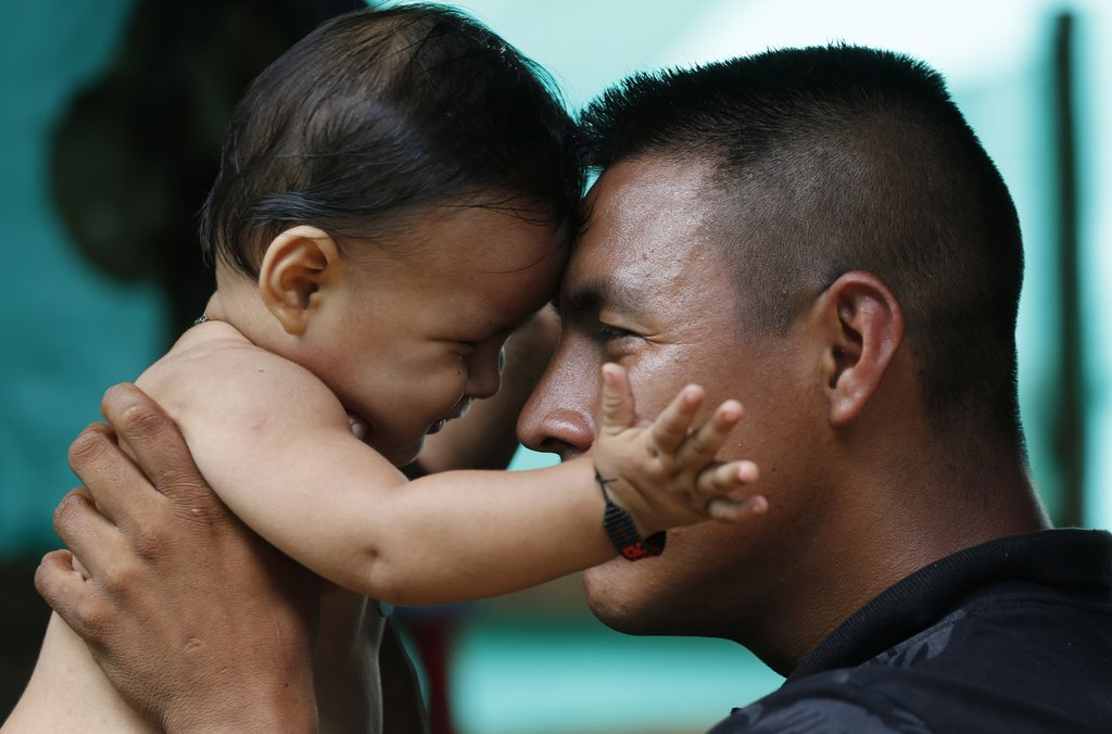 In this Tuesday, Feb. 28, 2017 photo, FARC rebel Vicente Pulecio plays with his 9-month-old son Dainer inside their tent at a rebel cam...