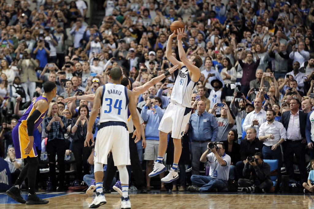 Dallas Mavericks' Devin Harris (34) watches as Dirk Nowitzki (41) of Germany takes a shot that sinks giving Nowitzki his 30,000th caree...