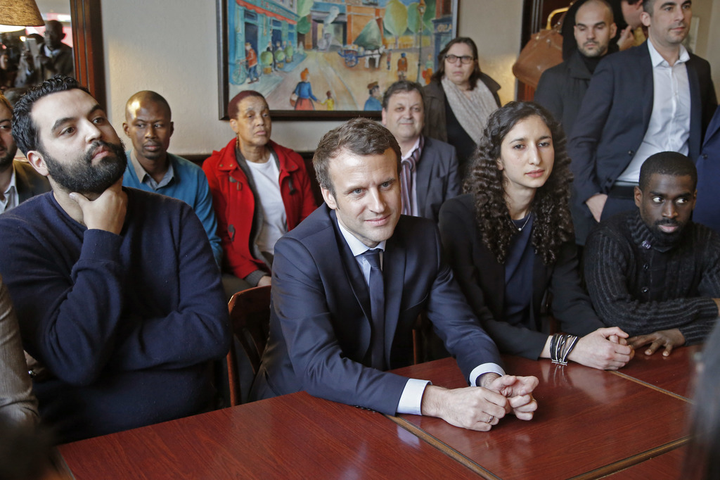 Independent centrist presidential candidate Emmanuel Macron listens to locals in a restaurent in Les Mureaux west of Paris, Tuesday, Ma...