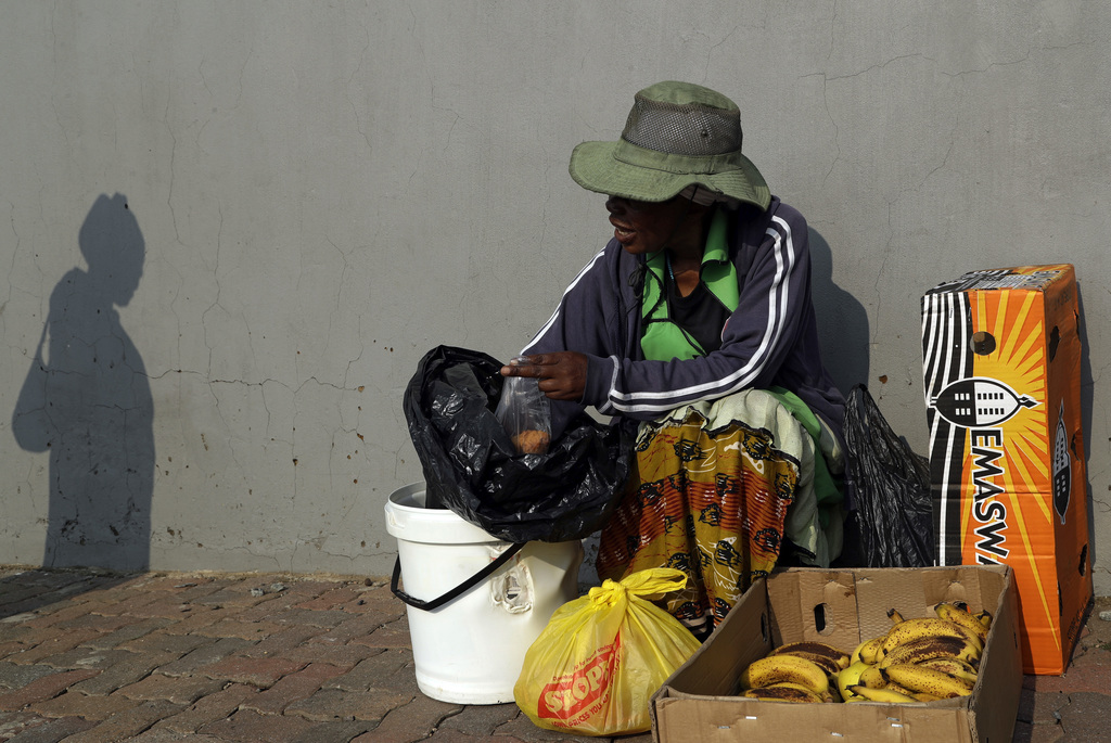 Maggie Malope, serves her client on a street corner of an industrial area in Alberton, east of Johannesburg, South Africa, Friday, Marc...