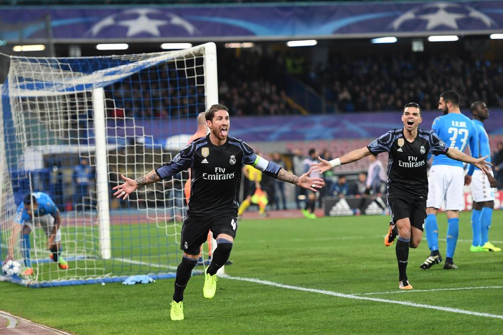 Real Madrid's Sergio Ramos, left, celebrates after scoring during a Champions League, round of 16, return-leg soccer match between Napo...
