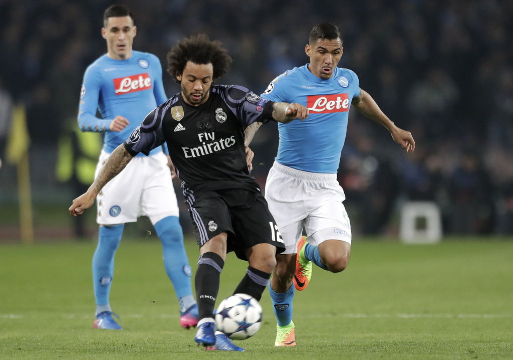 Real Madrid's Marcelo fights for the ball with Napoli's Allan during the Champions League round of 16, second leg, soccer match between...