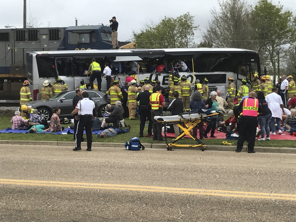Emergency personnel assist injured passengers after their charter bus collided with a train in Biloxi, Miss., Tuesday, March 7, 2017.  ...