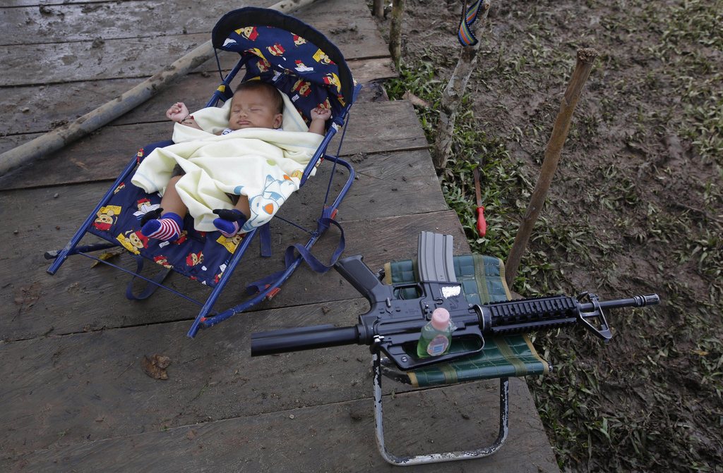 In this Tuesday, Feb. 28, 2017 photo, 3-month-old Junior Alexis Patino, son of FARC rebel Deisy Garcia, sleeps next to his mother's wea...