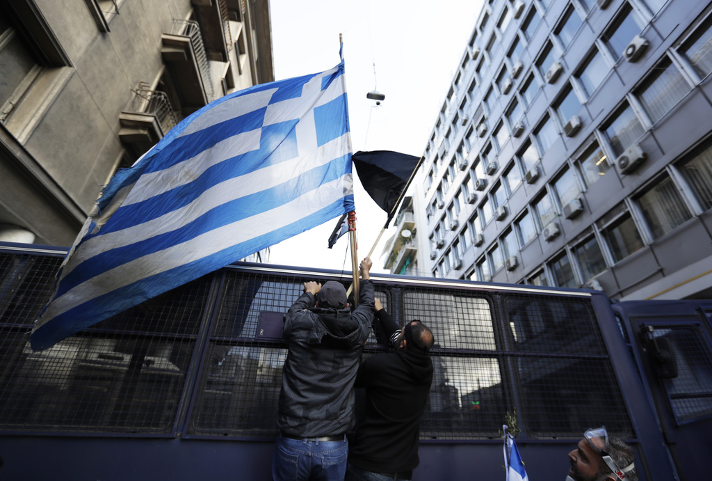 Protesting farmers place a greek flag on a police vehicle outside the Greek Agriculture Ministry, in Athens, Wednesday, March 8, 2017. ...